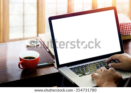 side view of the laptop is on the work table in a conner office with morning light.