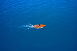 Side view of the speed boat. A large, orange speedboat moving on blue water. Aerial view of fast boat movement. Lonely boat, movement on the water.