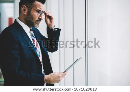 Side view of thoughtful confident proud ceo 50 years old looking out of window while updating website with financial news on tablet connected to 4G internet.Pondering successful trader with touch pad