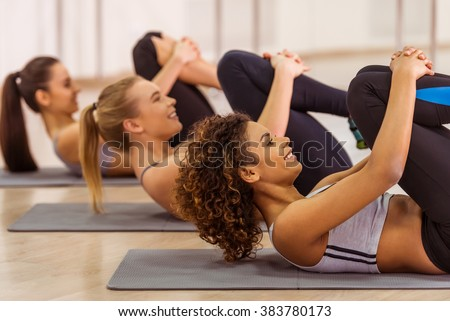 Side view of three attractive sport girls smiling while working out lying on yoga mat in fitness class