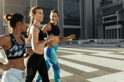 Side view of three fitness women in training clothes running outdoors. Smiling fitness runners jogging together in the morning.