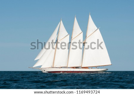 Side view of three-masted authentic windjammer or schooner passing by on a summer day wth blue sky. Windjamming is a popular attraction in New England for the tourism industry.