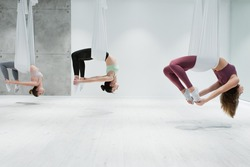 side view of three young women practicing aerial yoga in gym