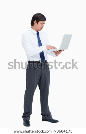Side view of tradesman working on his laptop against a white background