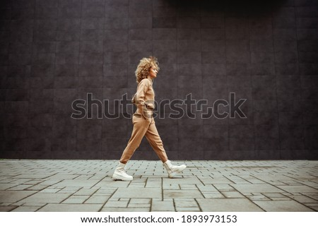 Side view of trap girl in tracksuit walking with hands in her pockets and listening music. Stock photo ©