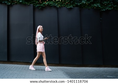 Side view of trendy female tourist walking around city enjoying holidays for exploring new area, positive millennial teenager with cellphone gadget in hands discovering world, concept of travel #1401118706