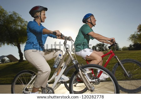 Side view of two Caucasian middle aged friends riding bicycle