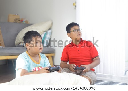 Side view of two concentrated young asian gamers playing game while sitting on the floor