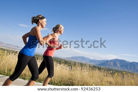 Side view of Two Female joggers running outdoors