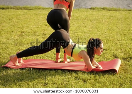 Side view of two fit young women doing pose on exercise mats #1090070831