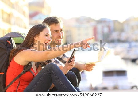 Side view of two happy tourists searching location together with a phone and map and pointing with the finger