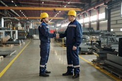 Side view of two male engineers in protective hardhats and workwear greeting one another by handshake in the morning in workshop