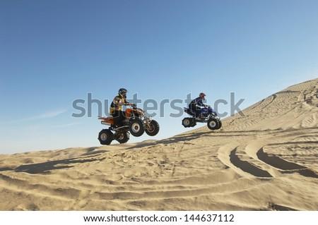 Side view of two men doing wheelies on quad bikes in the desert Stock photo ©
