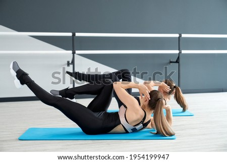 Side view of two unrecognizable fit women training abs on blue mats in ballet dance studio with handrails. Fitnesswomen with ponytails building abdominal muscles, practising crunches on floor. Foto stock ©