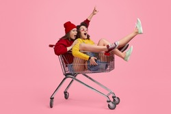 Side view of two young women screaming and riding shopping cart during race against pink background