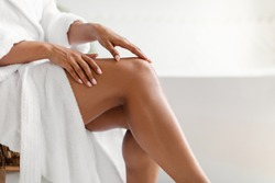 Side View Of Unrecognizable Black Lady Touching Perfect Smooth Legs After Depilation Posing Sitting On Chair In Bathroom At Home. Cropped Shot Of Female Legs. Hair Removal And Body Care