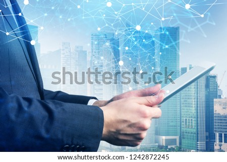 Side view of unrecognizable businessman holding tablet computer standing over cityscape background with double exposure of network hologram. Toned image