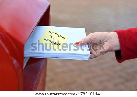 Side view of unrecognizable woman sending return to sander letters in envelope in red mail box Stockfoto ©