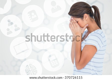 Side view of upset woman covering face against chemical structure in grey and white