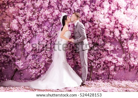 Side view of wedding couple kissing white standing against wall covered with pink flowers
