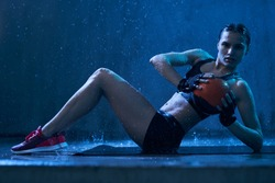 Side view of wet female bodybuilder in sports underwear doing exercise with small ball in hall, loft interior. Muscular woman training abs on mat under rain in blue dark atmosphere, looking at camera.