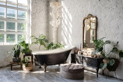 Side view of white cozy bathroom with black tub, wooden classic commode, mirror, decor, plants and interior design in boho chic style. Concept of comfortable and decorated room at home