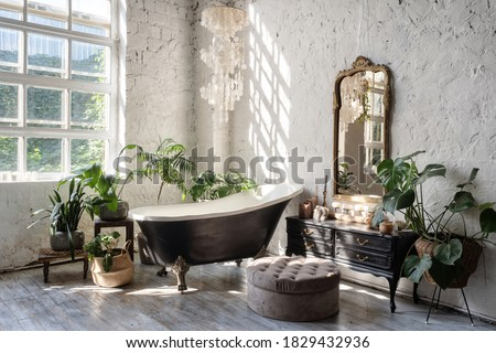 Side view of white cozy bathroom with black tub, wooden classic commode, mirror, decor, plants and interior design in boho chic style. Concept of comfortable and decorated room at home Stockfoto ©