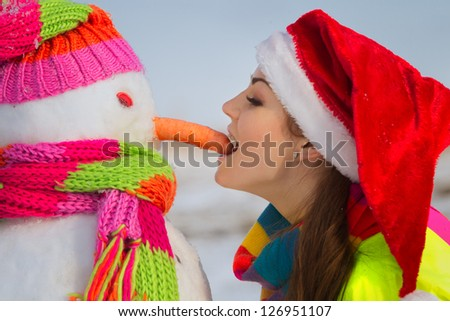 Side view of woman  biting off snowman`s nose  on a warm winter day