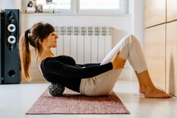 Side view of woman in sportswear using duoball for myofascial release exercise for spine lying on yoga mat at home or office, overcome pain, rehabilitation concept.