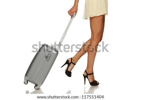 Side view of woman legs with a suitcase on the white background