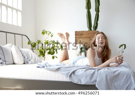 side view of woman lies in bed with cupp of coffee Stok fotoğraf ©