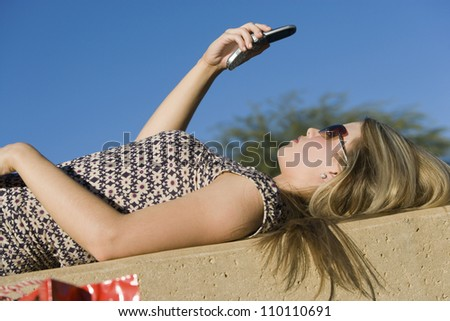 Side view of woman lying on back reading text message through cell phone