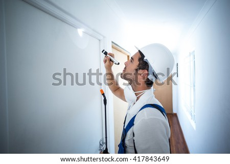 Side view of worker using flashlight in hallway at home