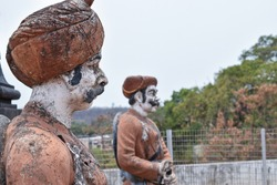 Side view of 30-40 years old Indian warrior statue wearing orange color turban and Indian traditional cloths standing still in a sunny day at kolhapur city Maharashtra india focus on front object