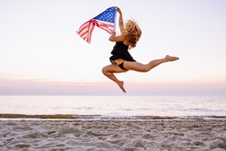 Side view of young active woman holding american flag and jumping on beach. Visa, green card, travel concept