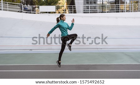 Side view of young adult girl in sportswear and sneakers shoes warming up, jogging on cardio workout, spending day on sport training outdoor in city