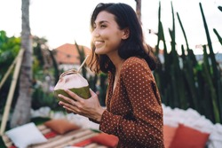 Side view of young attractive ethnic female enjoying coconut drink through straw and smiling happily while standing in yard of resort house on sunny evening