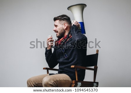 Side view of young attractive movie director shouting on the megaphone while sitting on the chair isolated on grey background. Man directing film process #1094545370