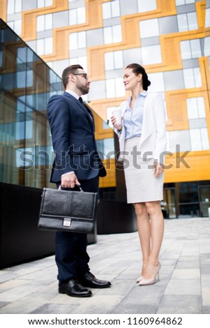 Side view of young attractive successful people having good conversation in business dress near office building