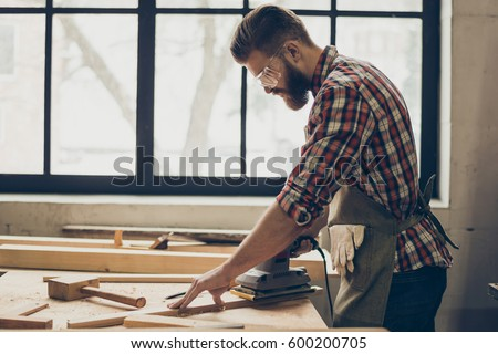 Side view of young bearded craftsman with sander grinding a wooden plank at his workshop Сток-фото ©