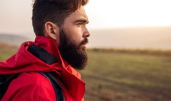 Side view of young bearded male hiker in warm red jacket looking away while standing against blurred green field during trekking in autumn countryside
