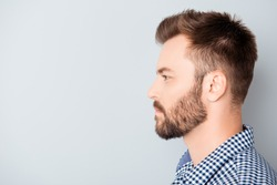Side view of young bearded man isolated on gray background