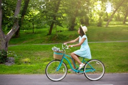 Side view of young black woman going for ride on bike at park in summer, empty space