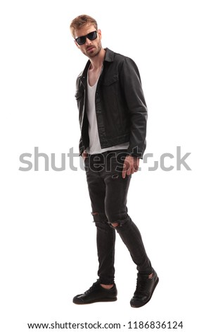 side view of young blond man wearing sunglasses and leather jacket stepping to side on white background, full body picture
