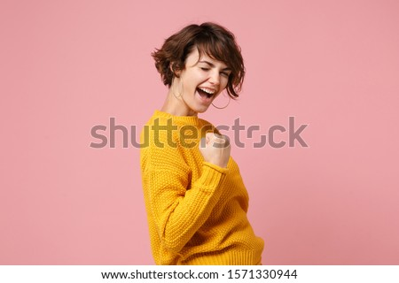 Side view of young brunette woman girl in yellow sweater posing isolated on pastel pink background studio portrait. People sincere emotions lifestyle concept. Mock up copy space. Doing winner gesture