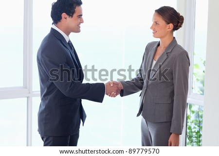 Side view of young business partner shaking hands