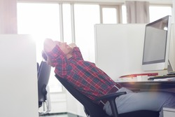 Side view of young businessman relaxing at computer desk in office