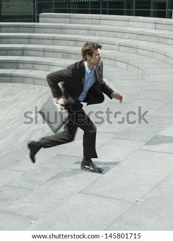 Side view of young businessman with briefcase running upstairs outdoors
