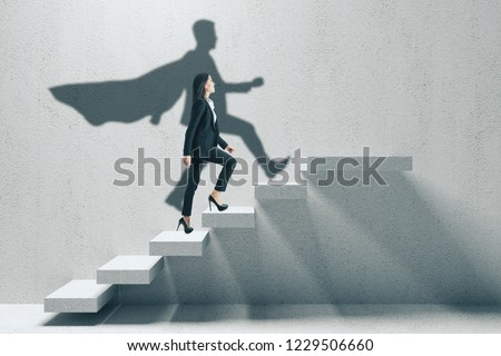 Side view of young businesswoman with hero shadow climbing concrete stairs. Career development and confidence concept. #1229506660