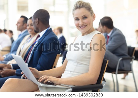 Side view of young Caucasian female executive using laptop during in conference room, smiling to camera. Executives in the background.  #1439502830